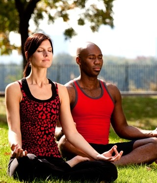 Two people meditate in the park.